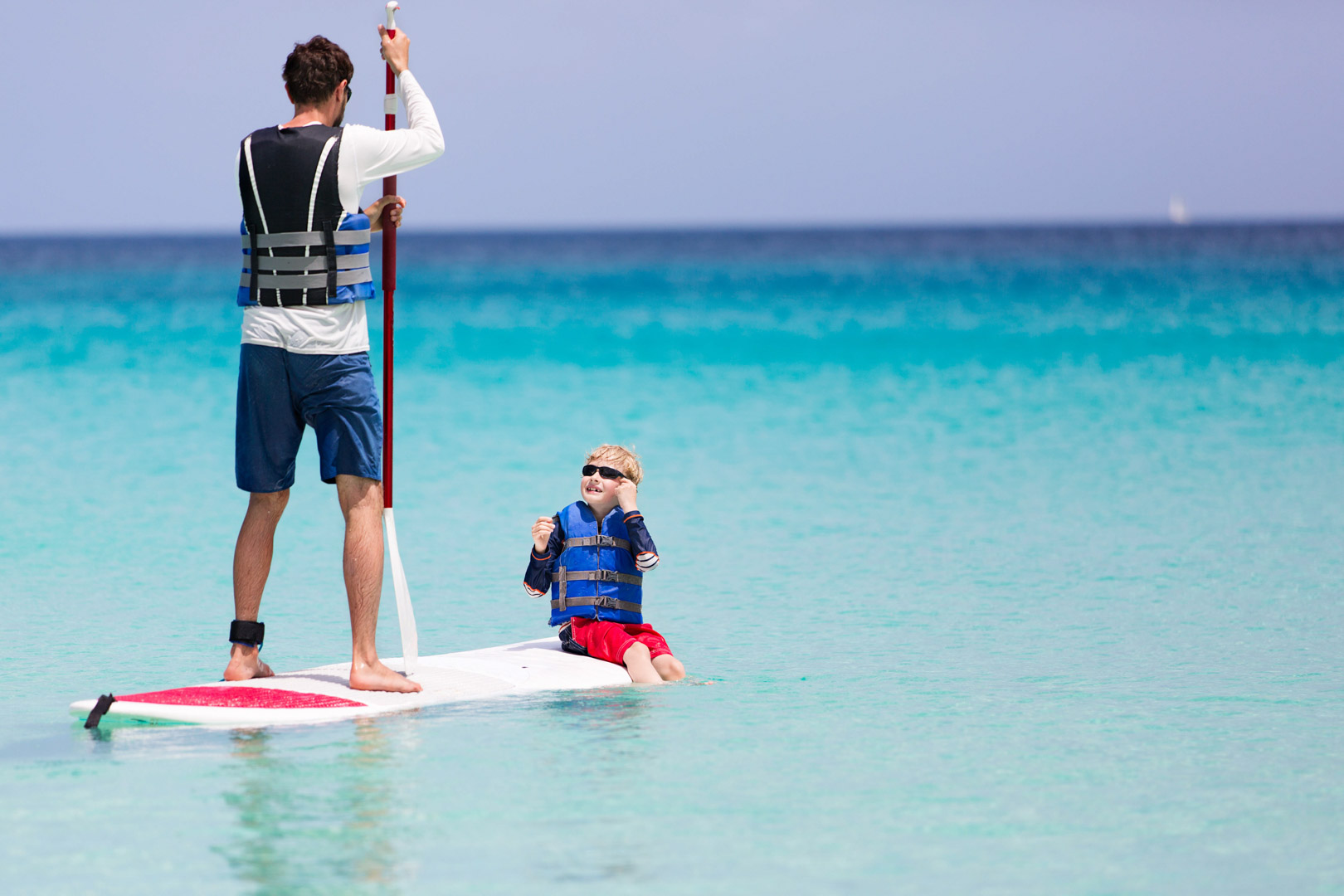 man paddle boarding with a little kid in the ocean