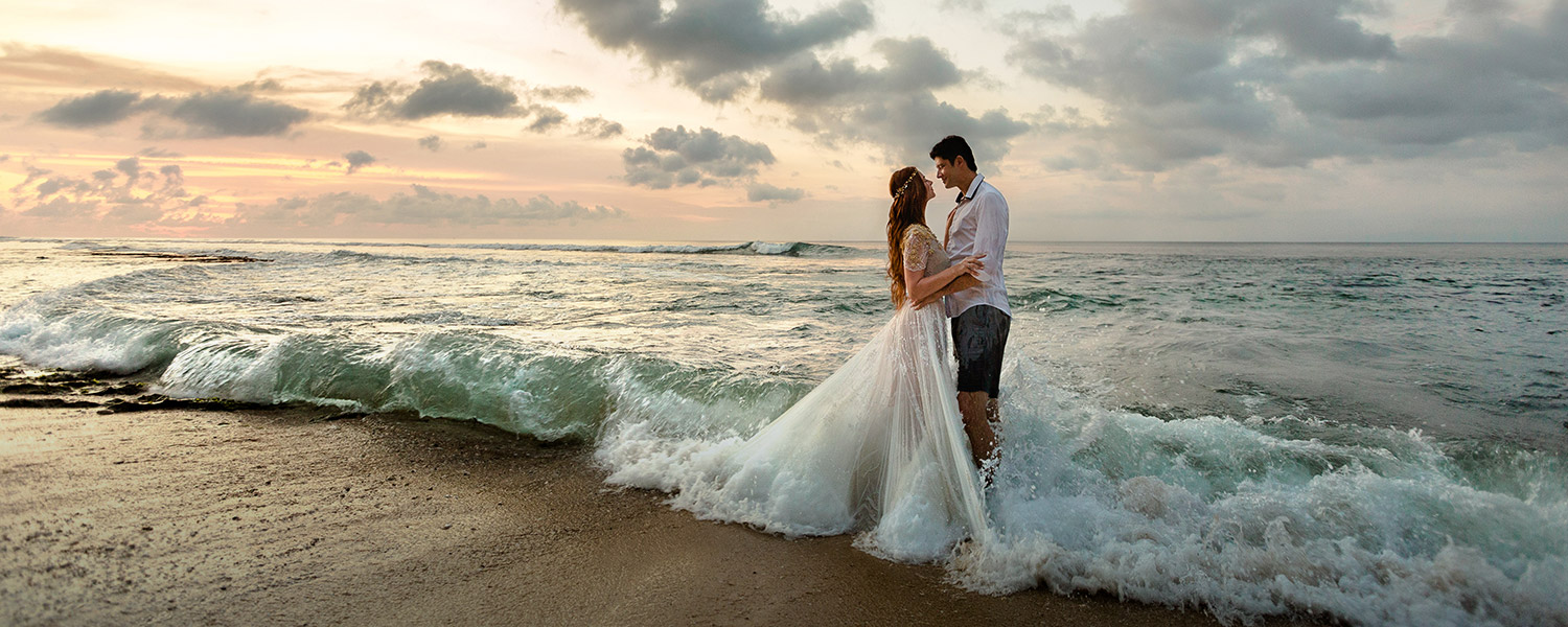 bride and groom with full wedding outfits in the ocean water