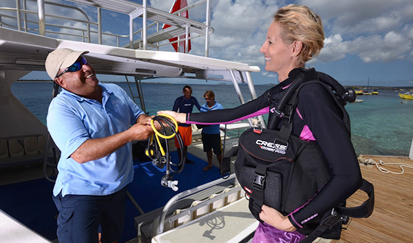 a blonde woman getting on a boat to scuba dive