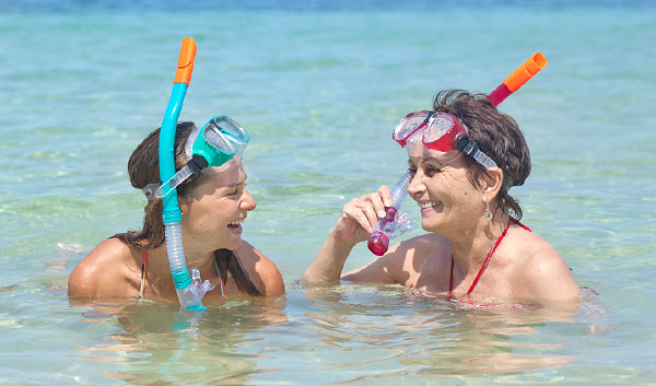 two girls sitting in shallow water with snorkel gear on