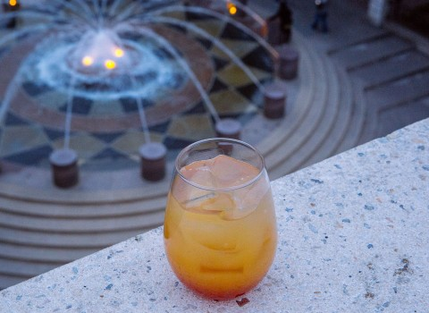 cocktail on a ledge with fountain below