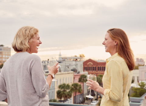 two women enjoying a glass of wine at HarbourView Inns Rooftop Bar