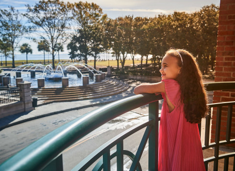 Young girl looking out to the water fountain from HarbourView Inns balcony