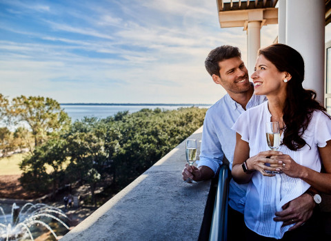 Couple holding each other and having a glass of champagne on their balcony