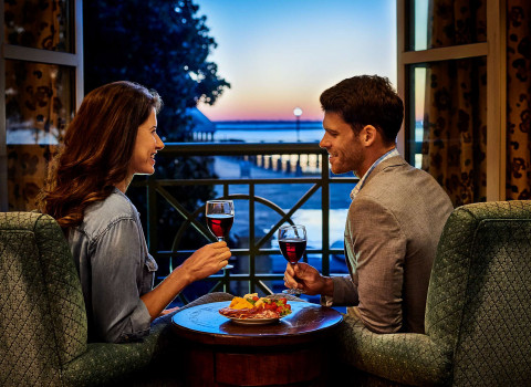 couple enjoying wine and cheese infront of a window with a waterfront view