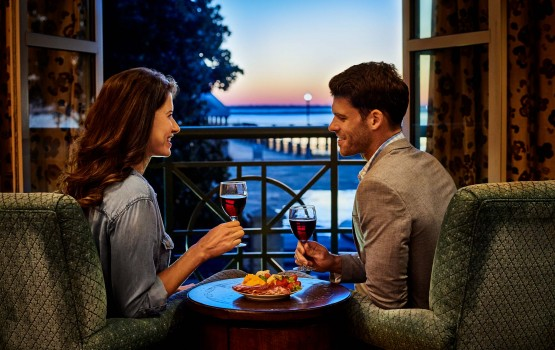 <couple drinking wine with balcony view