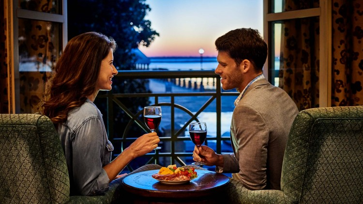 couple drinking wine with balcony view