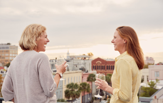 <two women on a rooftop having wine