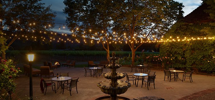 Outdoor terrace with metallic seating and lightbulbs strung
