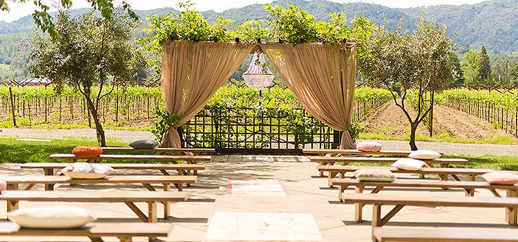 Rows of wooden benches facing arc with burlap decor