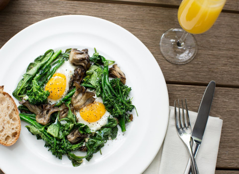 dish of two over easy eggs spinach and mushrooms with a mimosa