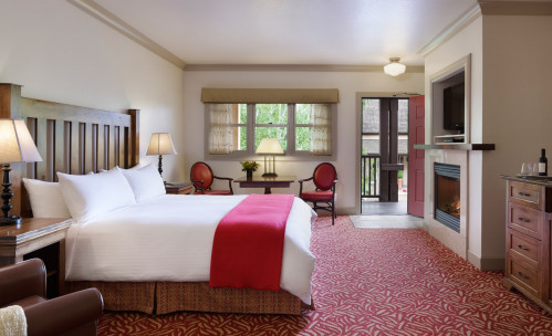 King bedroom with a red bedspread and sitting area