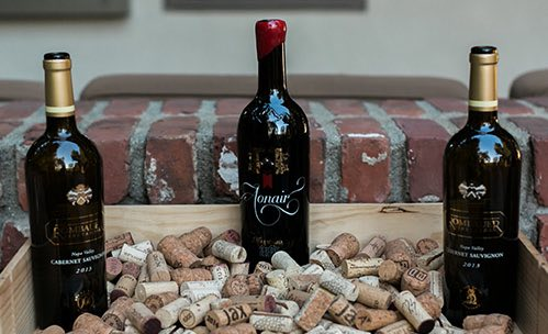 Three wine bottle surrounded by corks
