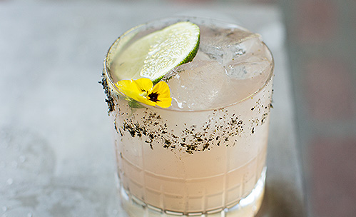 Light pink cocktail with a cucumber and salt on the rim