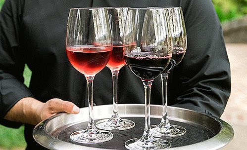 Server holding four glasses with red wines on silver platter