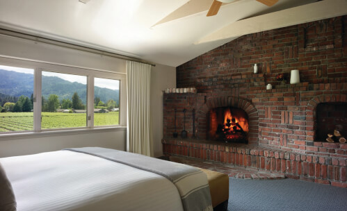Bed facing brick fireplace next to window with vineyard view