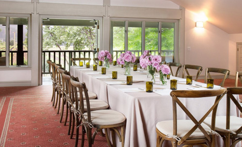 A long table with wooden chairs set up for a dinner reception