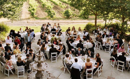 Overhead view of people seated at round tables outside for reception