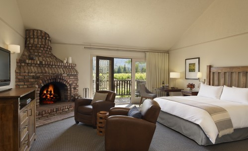 Vineyard View room with cozy fireplace and seating, and king bed with wooden headboard