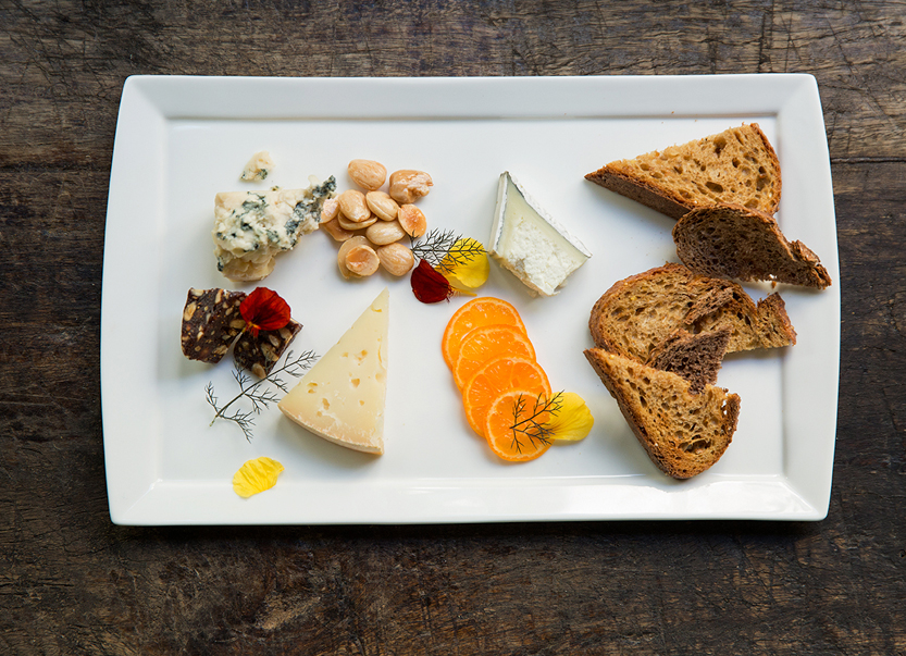 cheeses and bread on a white plate