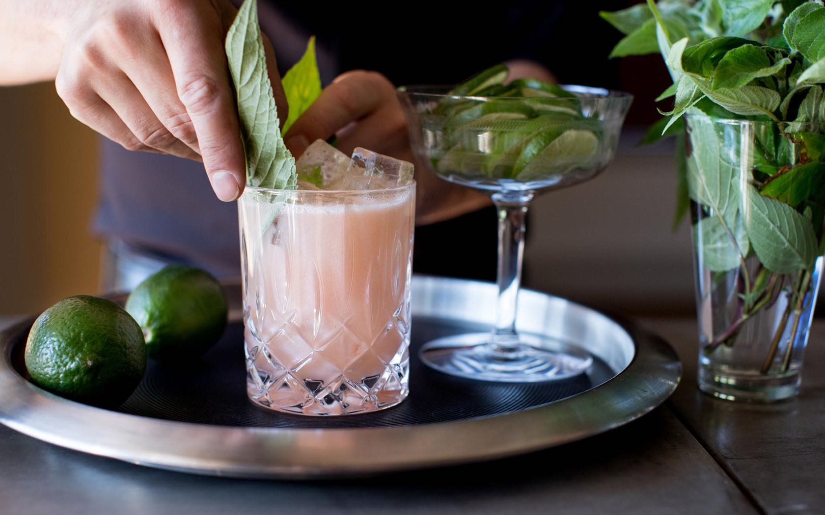 Bartender placing leaves in cocktail on the rocks