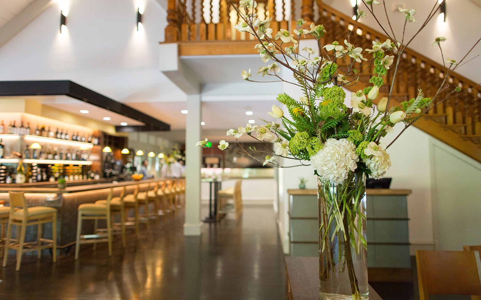 White flower arrangement with bar in the background