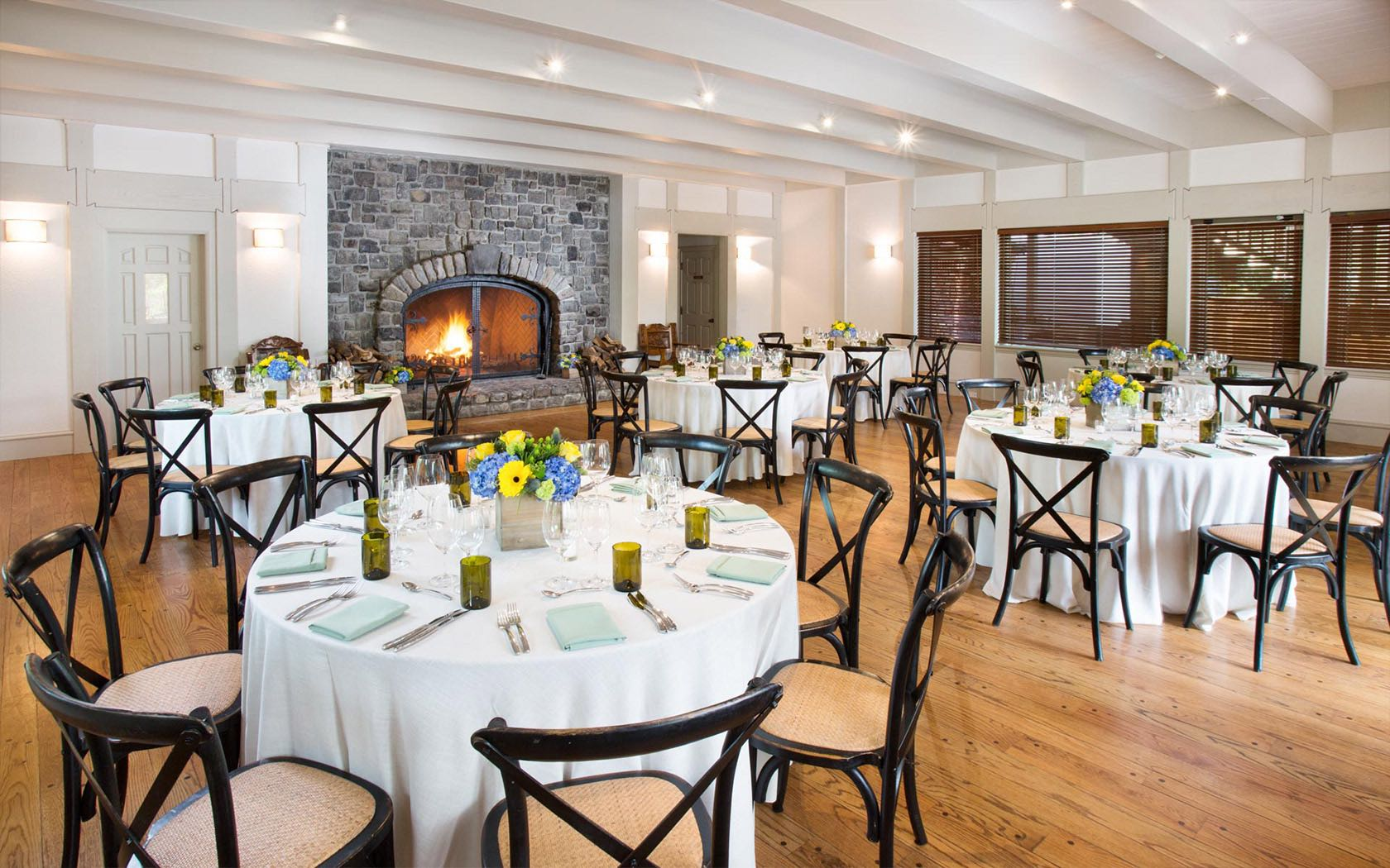 Event space with fireplace set up with round tables for reception