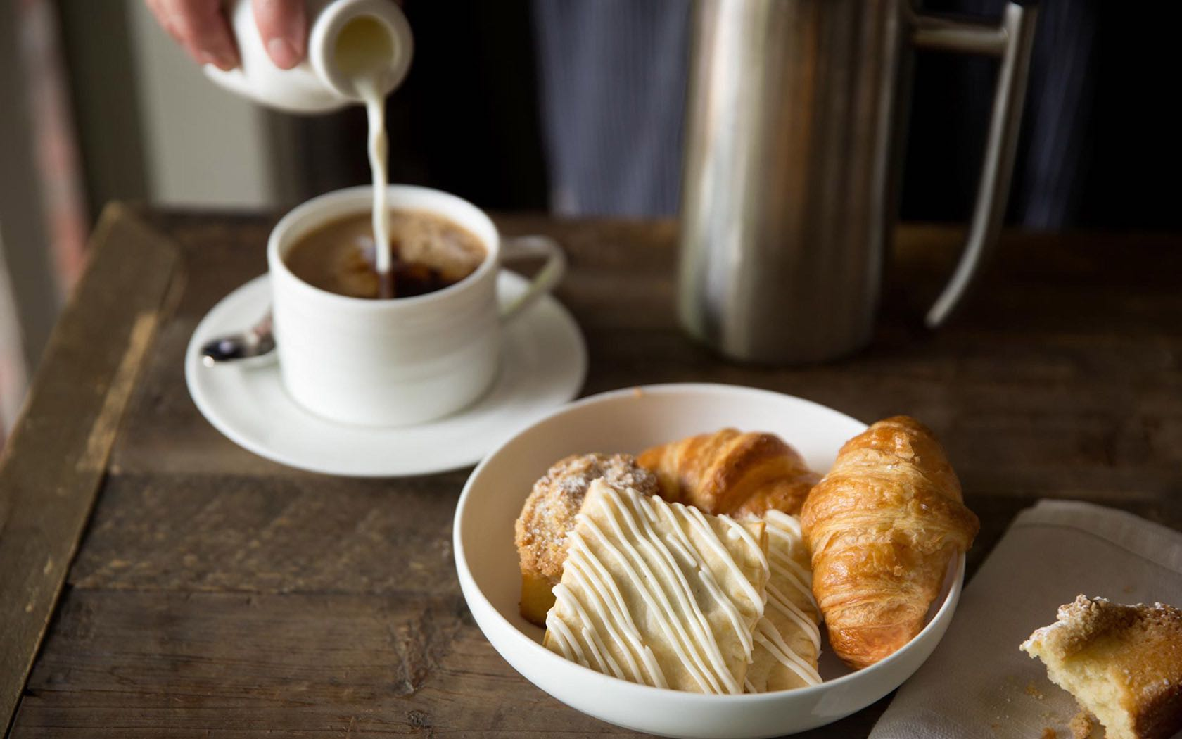 Coffee being poured into mug next to plate of pastries