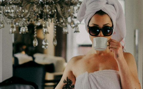 woman drinking a cup of coffee with sunglasses and a towel on her head