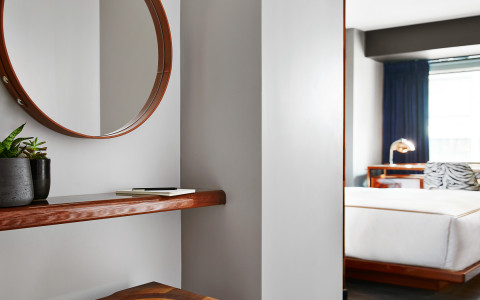 round mirropr on wall and view of bed
