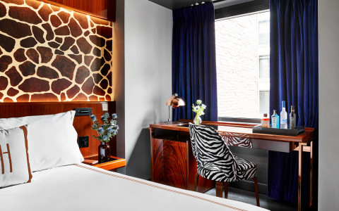 Queen bed with a desk and zebra stamp chair