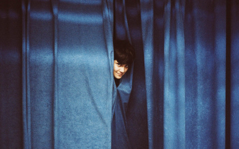 woman behind blue curtain