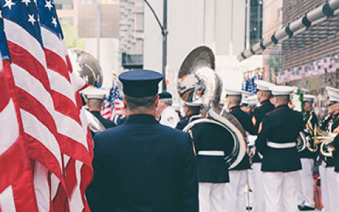 military men in uniform walking down the streets holding the American flag and large instruments