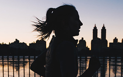 a woman running next to a body of water in central park at dusk