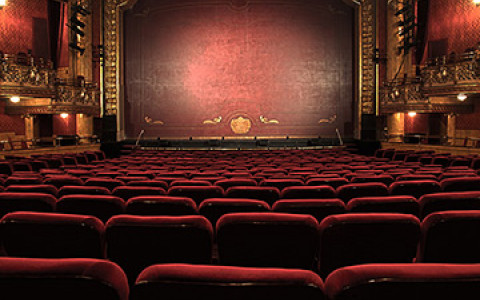 an empty theater with red seats facing a stage