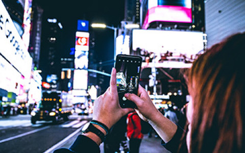 a woman taking a picture on her iphone of times square lit up at night