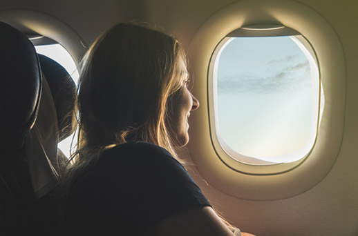woman starring out the window of a plane