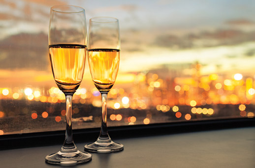 two champagne glasses against the ny skyline
