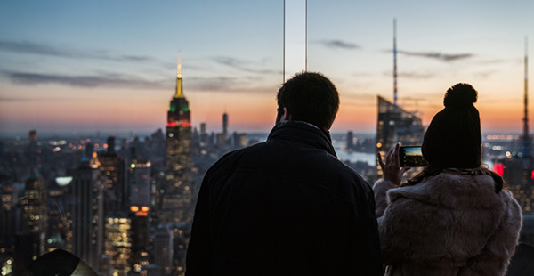 a man and woman standing on a rooftop building looking out over the new york city buildings at night