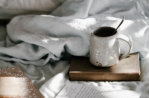 a coffee mug sitting on a wooden platter on a messy bed
