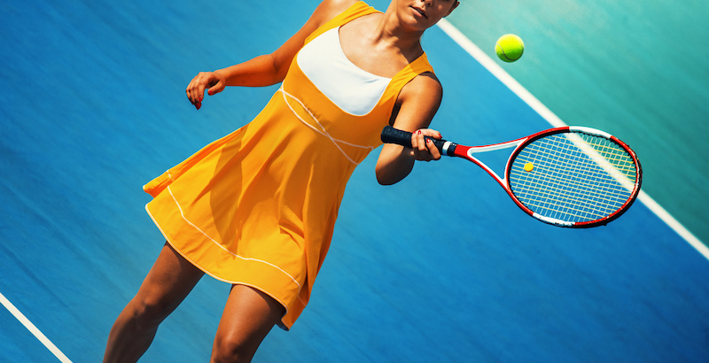 female playing tennis on blue court