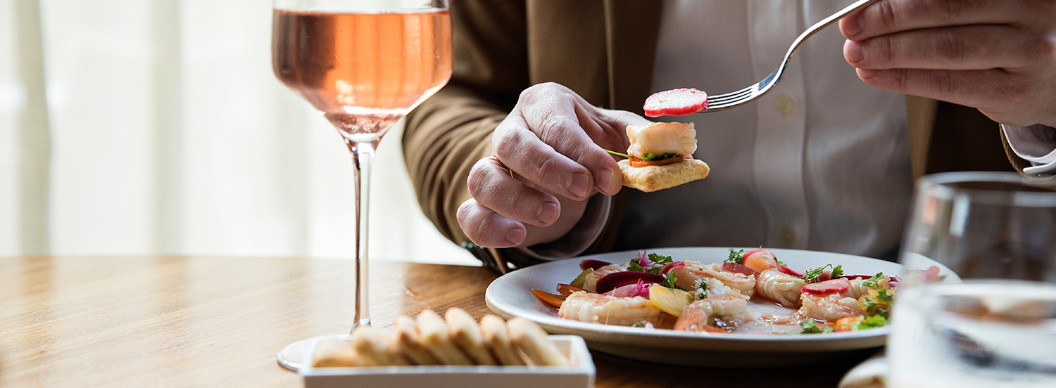 person holding appetizer in front of glass of rose