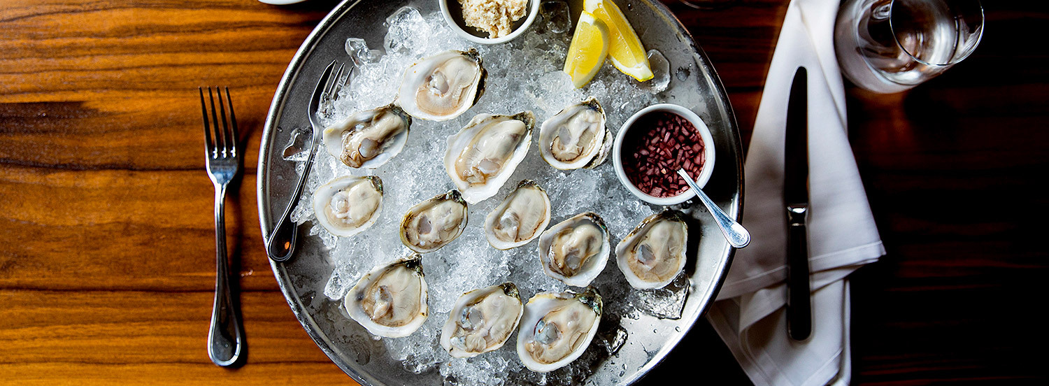 raw oysters on ice with cocktail sauce and a lemon