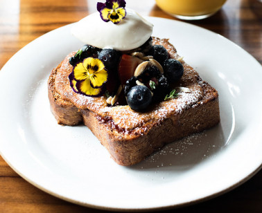 french toast topped with berries and edible flowers