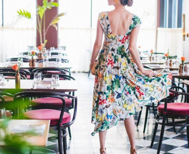 woman in floral dress posing in main dining area