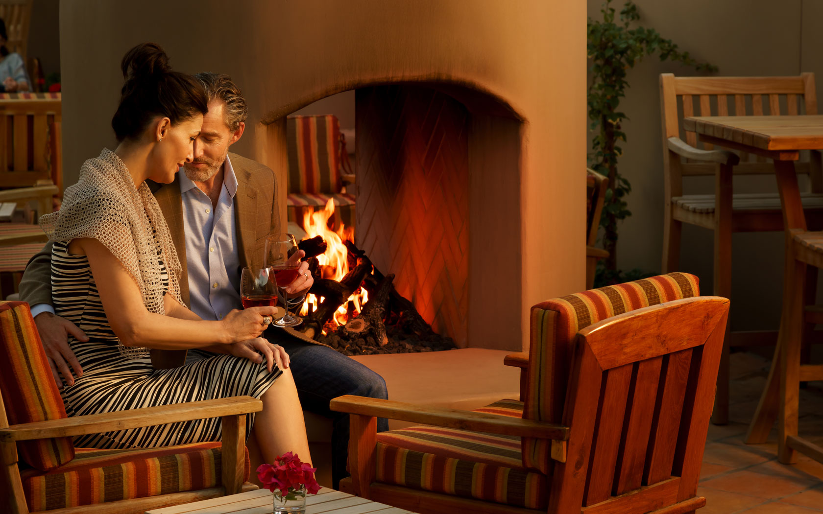 Couple drinking wine by fireplace