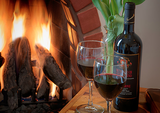 Glasses with red wine next to fireplace