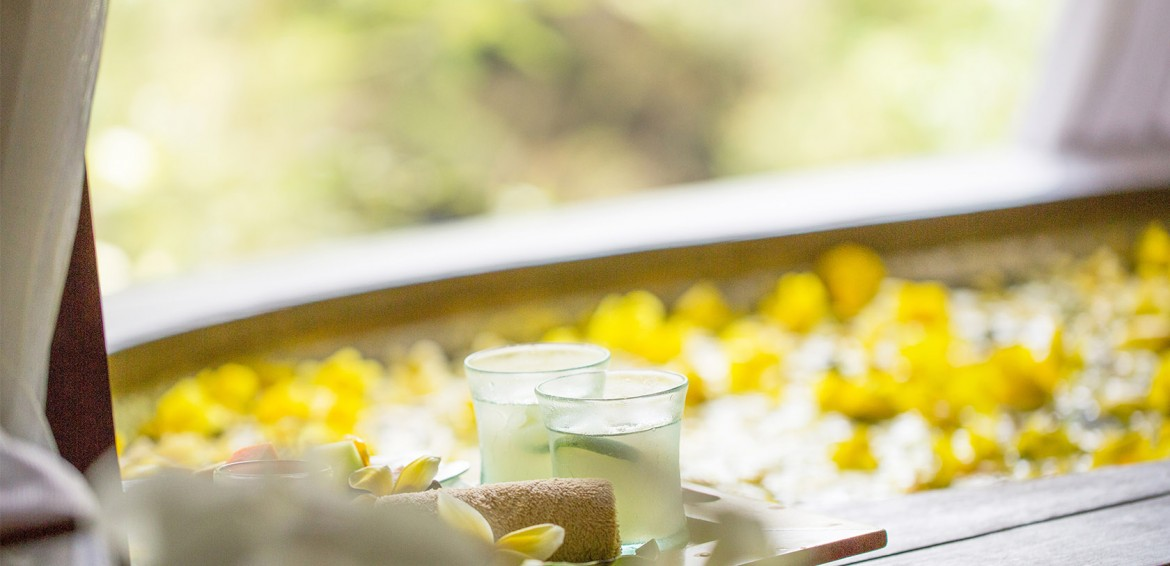 Spa tub with yellow flowers and cucumber water