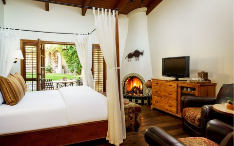 Room with double bed, outdoor terrace, leather chairs, TV & fireplace