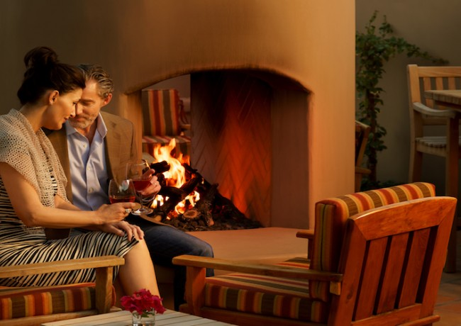 Couple enjoying drinks near fireplace outdoors